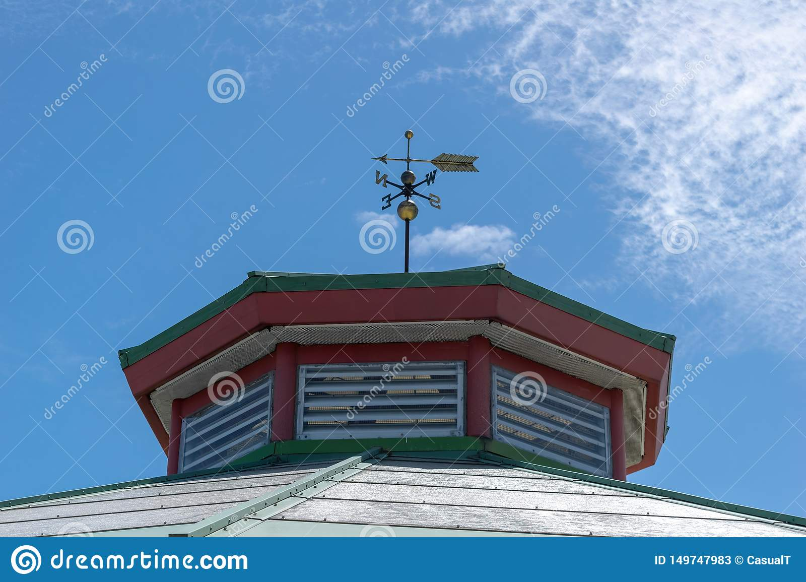 A weather vane atop an old building, against a blue sky with some light fluffy clouds