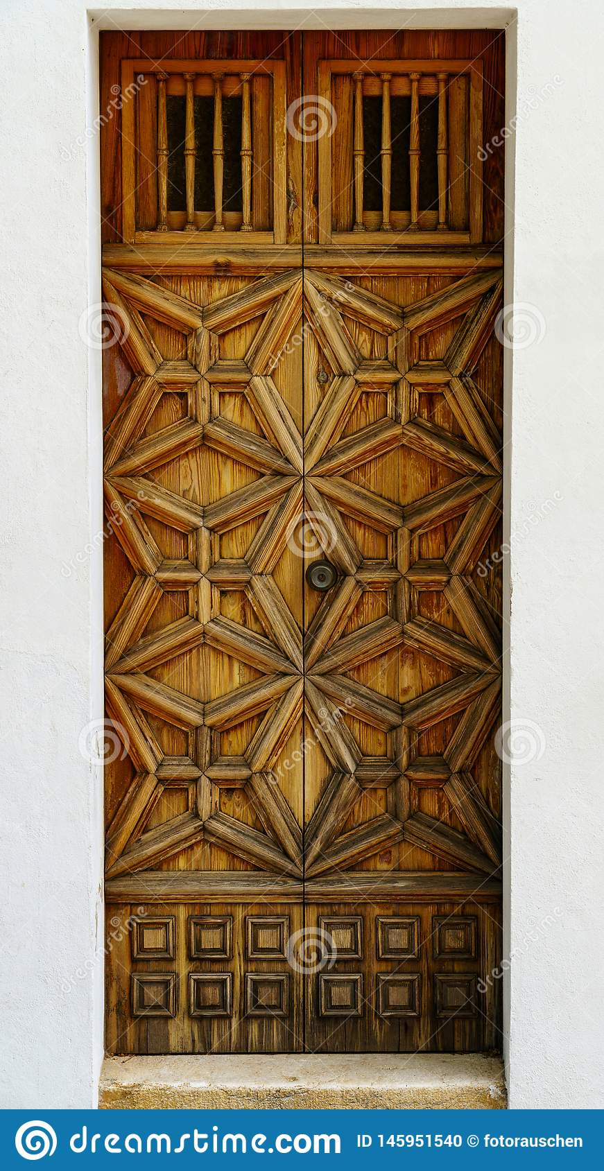 Weathered wooden front door with ornate decor