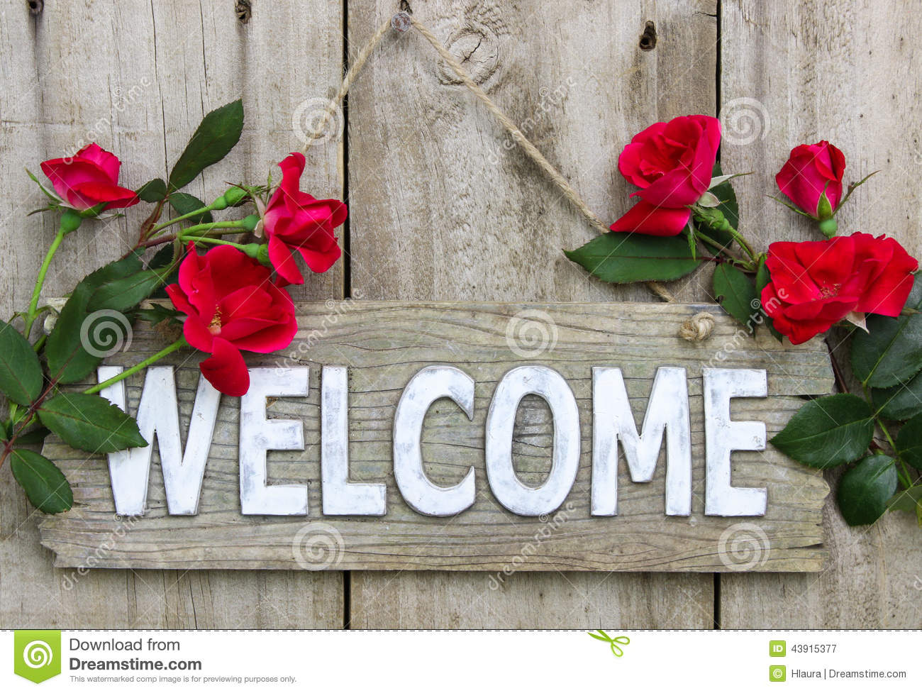 Weathered Welcome Sign With Red Flowers Hanging On Old