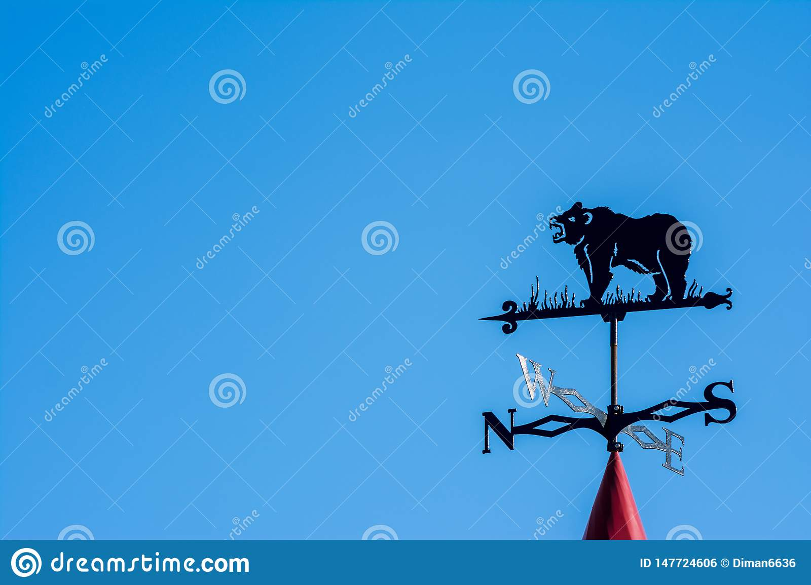 Weathervane in the form of a bear. Side of the world against the sky