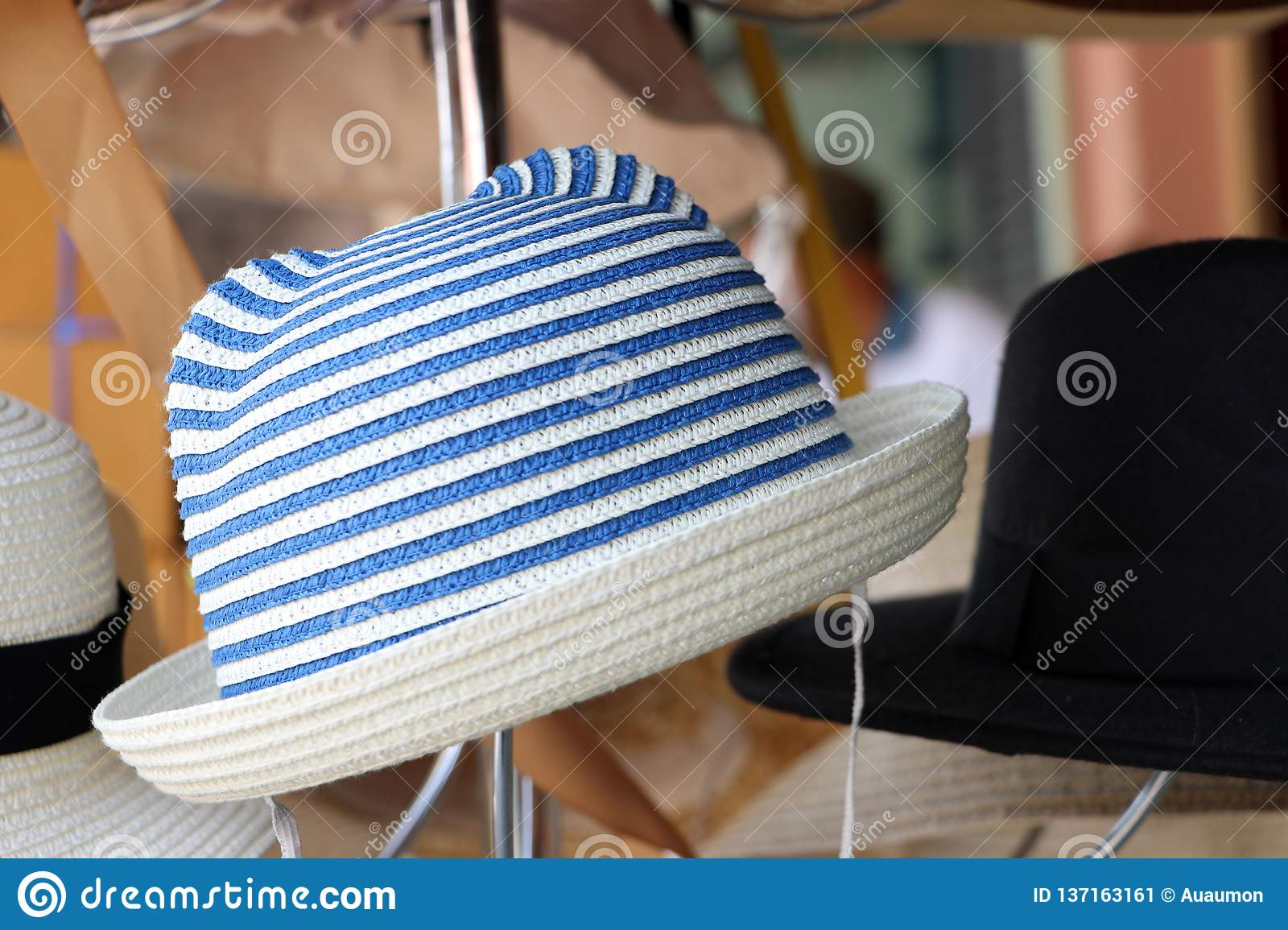 Weave hat on horizontal Stripes of blue and white color hanging on the hat hanger for sale