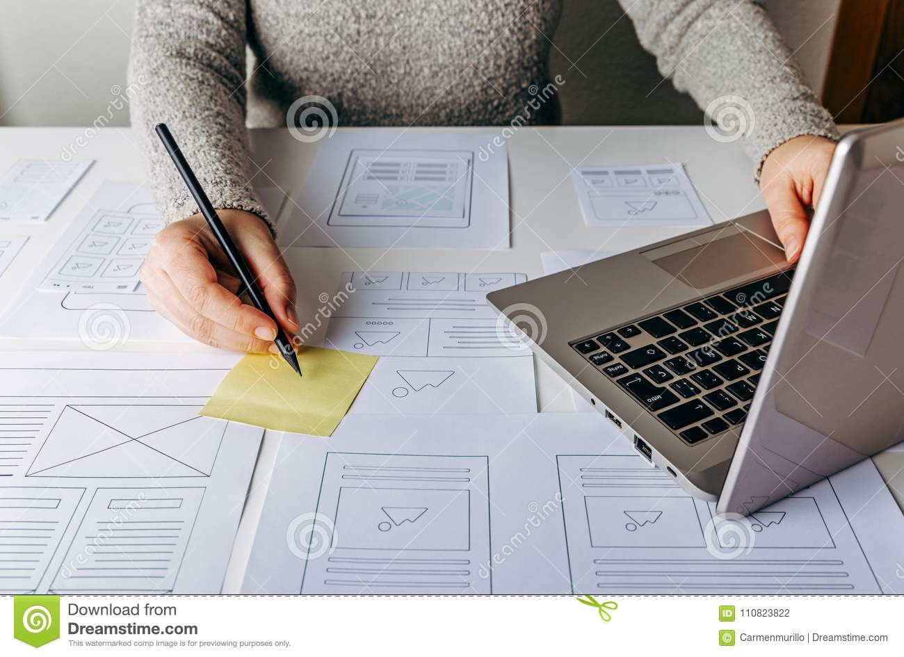 Web designer working at laptop and website wireframe sketches