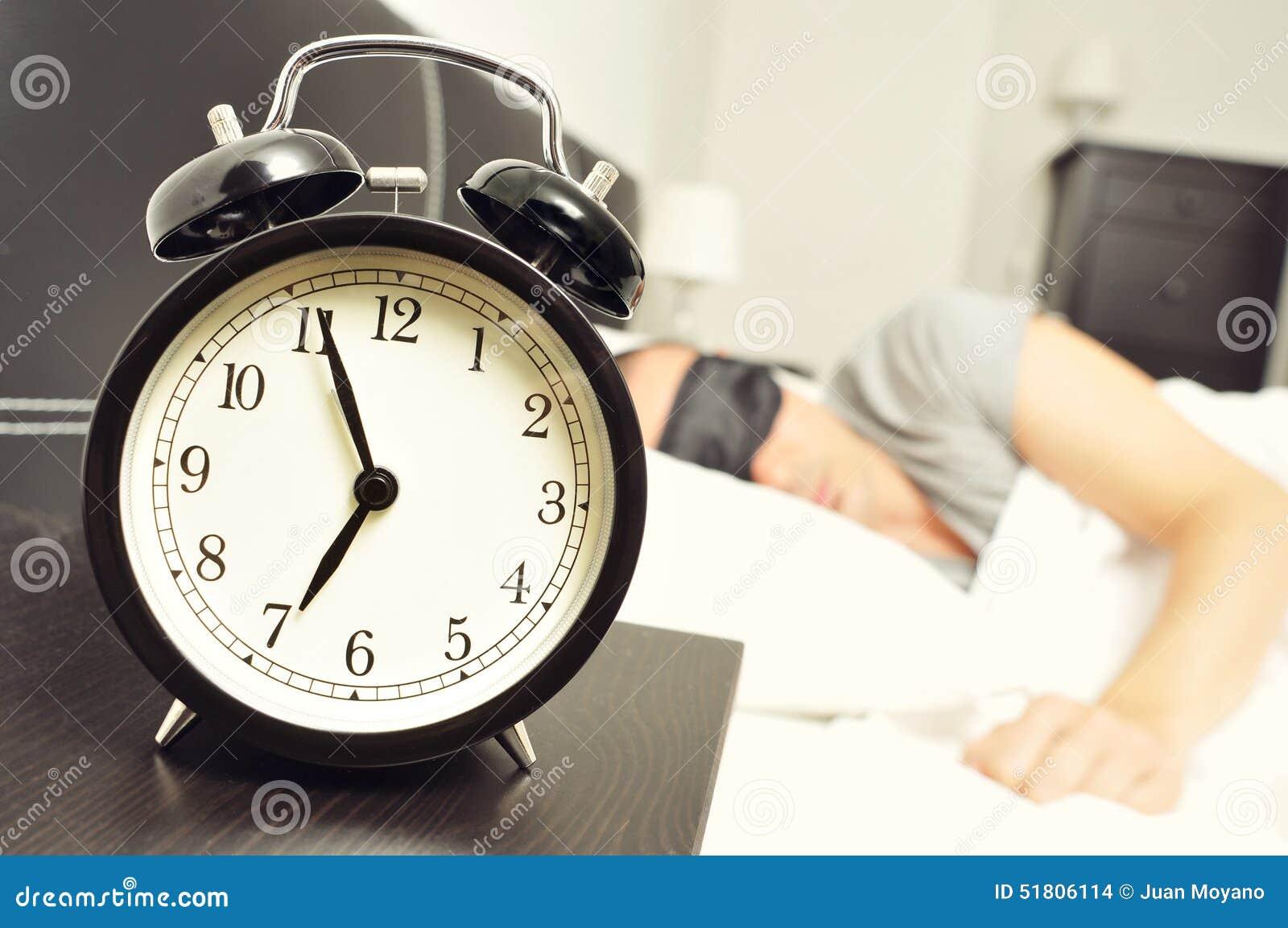 wecker und junger mann die im bett mit einer schlafmaske. Black Bedroom Furniture Sets. Home Design Ideas