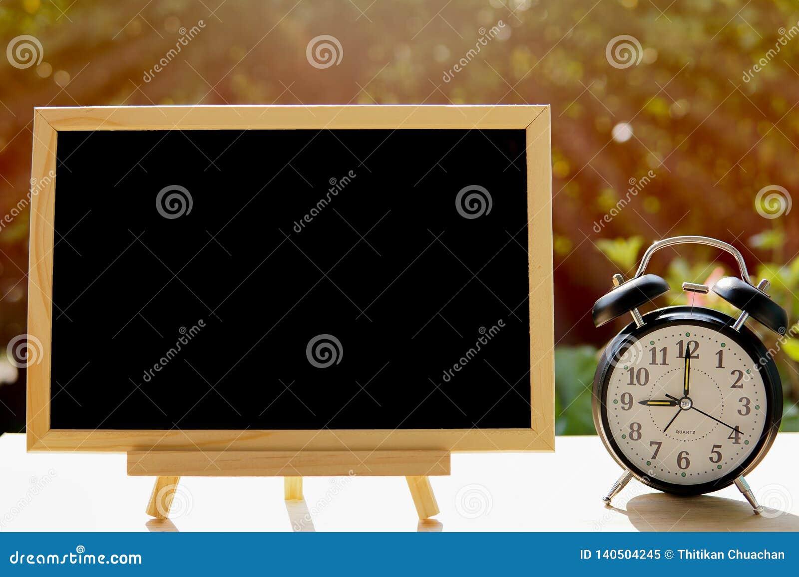 Wecker und Tafel oder Tafel im allgemeinen Park für Ihren Textbrettplan mit Zeitkonzept