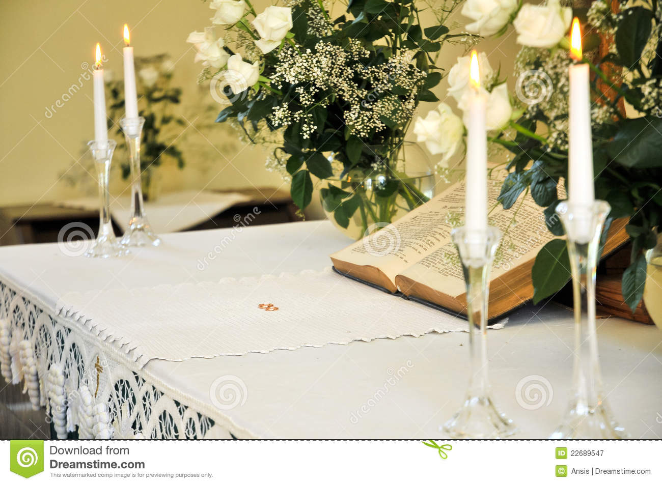 Wedding altar with rings bible candles and roses