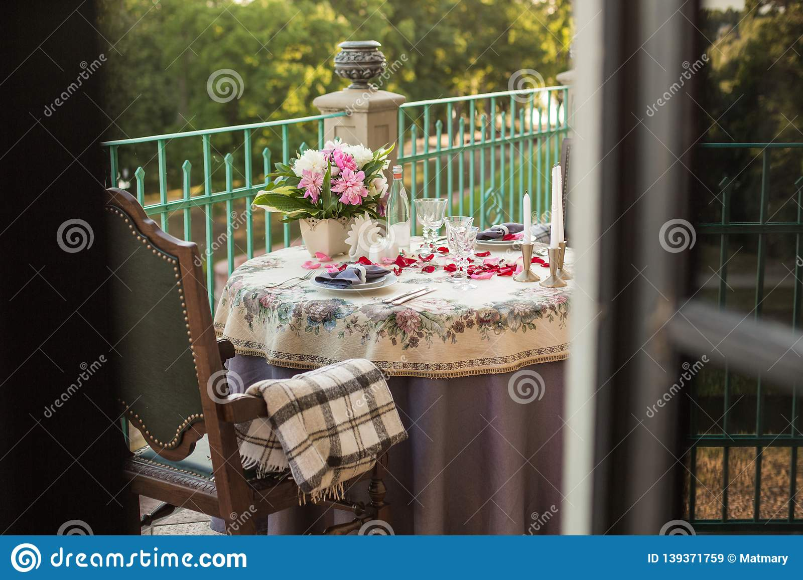 Romantic decor of the festive table in the restaurant with candles, flowers, rose petals