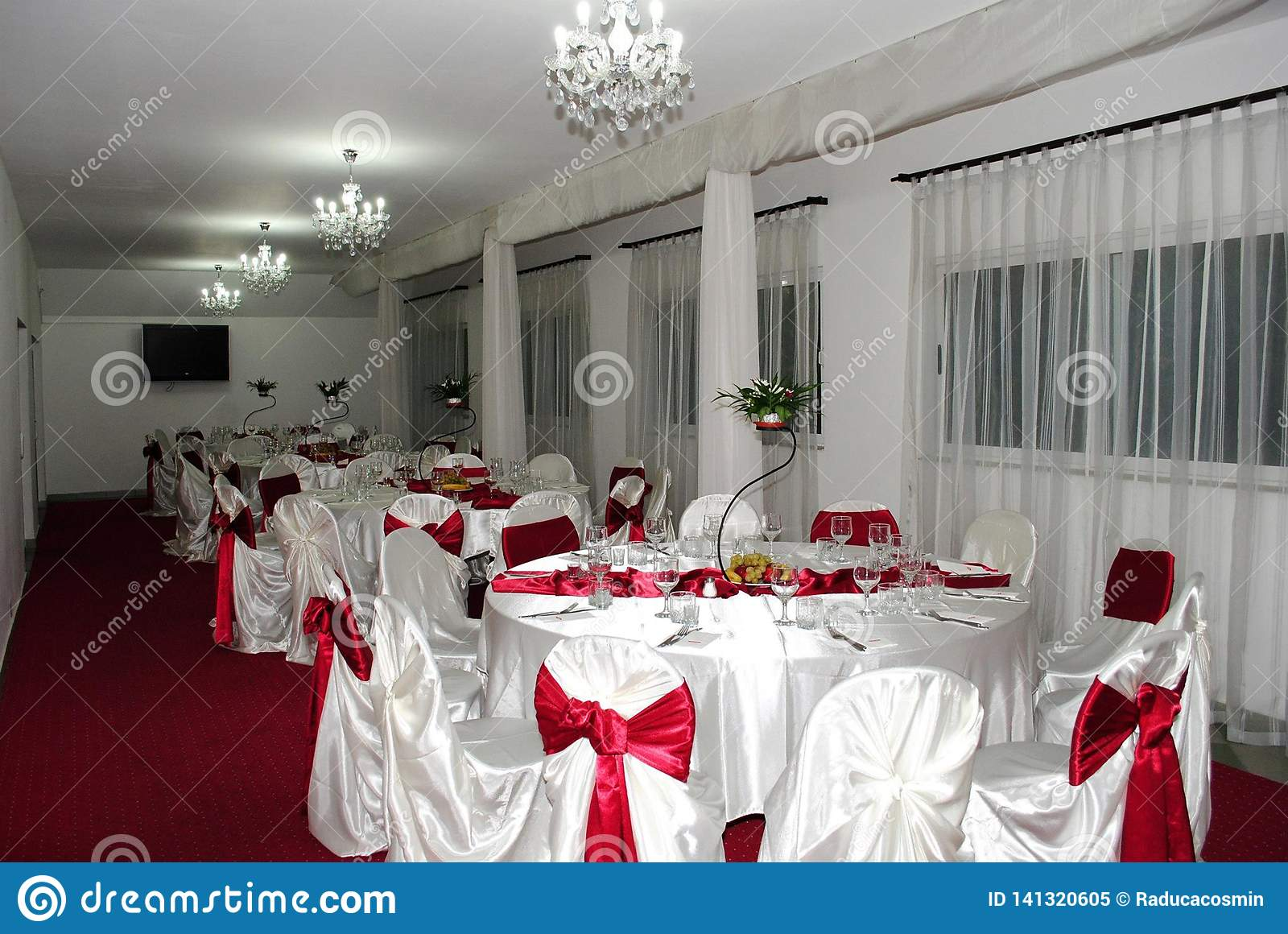 Wedding arrangement with beautiful chandelier and white and red chairs