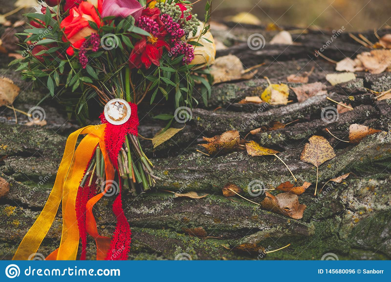 Wedding autumn bouquet of the bride on the tree. Beautifully decorated with satin ribbons and jewelry bouquet of several kinds,