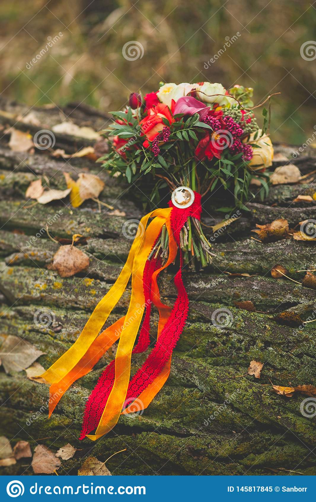 Wedding autumn bouquet of the bride on a tree covered with moss. A bouquet of different flowers is beautifully decorated with