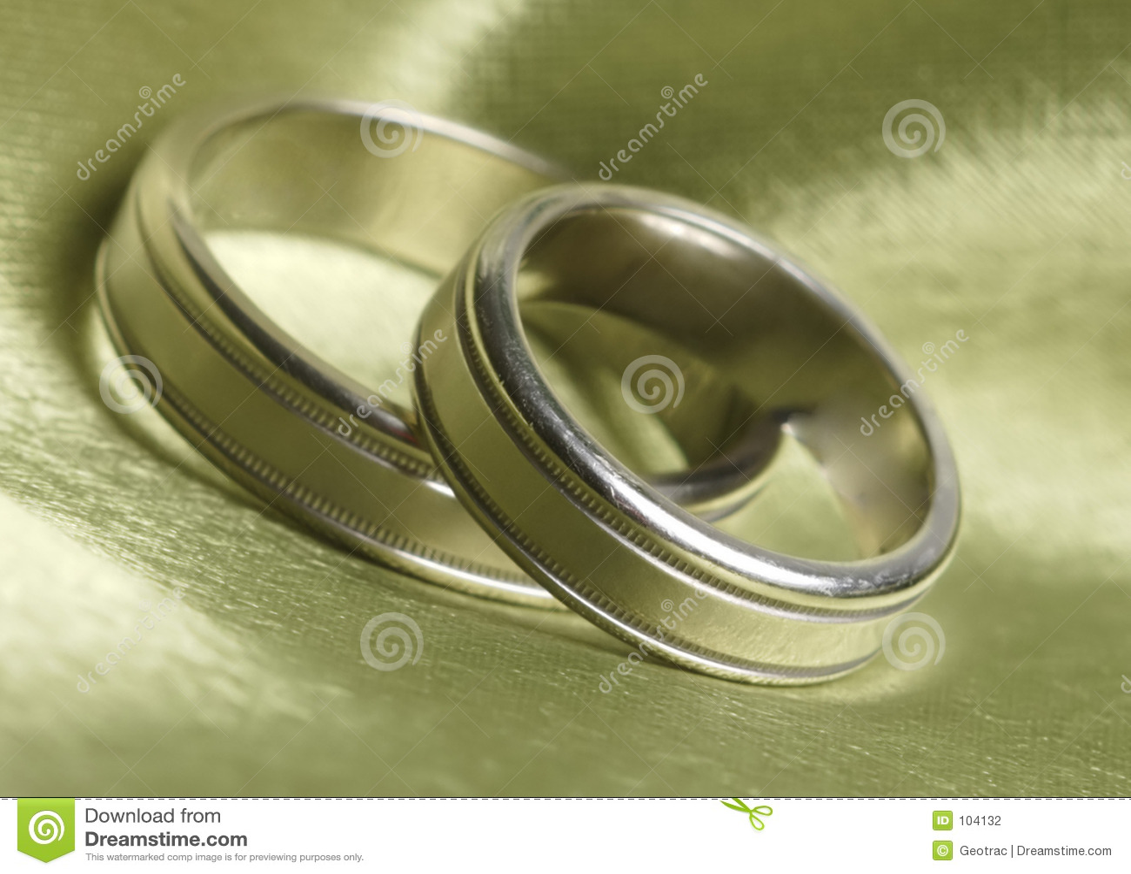Wedding bands up close on green satin