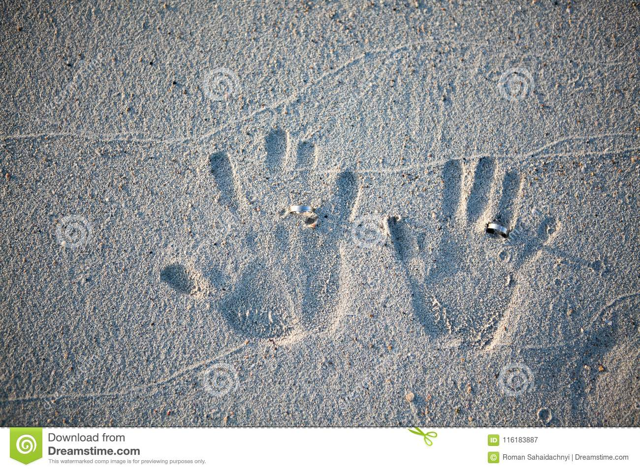 Finger prints of the bride and groom with wedding rings on the sand of the beach.