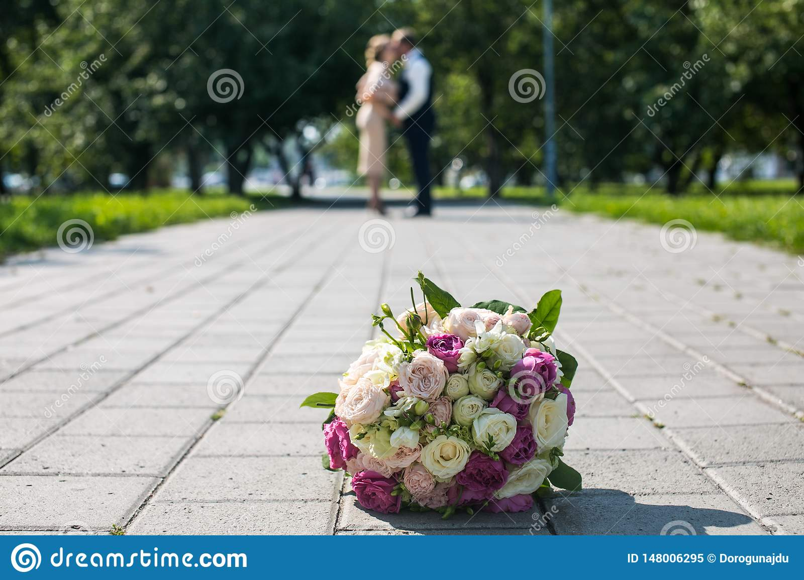 Wedding bouquet and the newlyweds in the park a beautiful wedding
