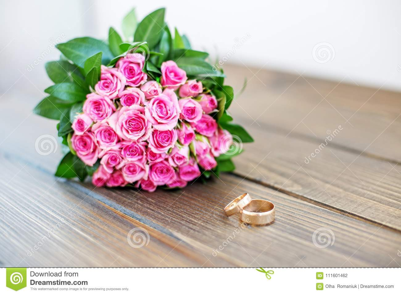 Wedding Bouquet Of Pink Roses And Wedding Rings On A Wooden Tabl ...