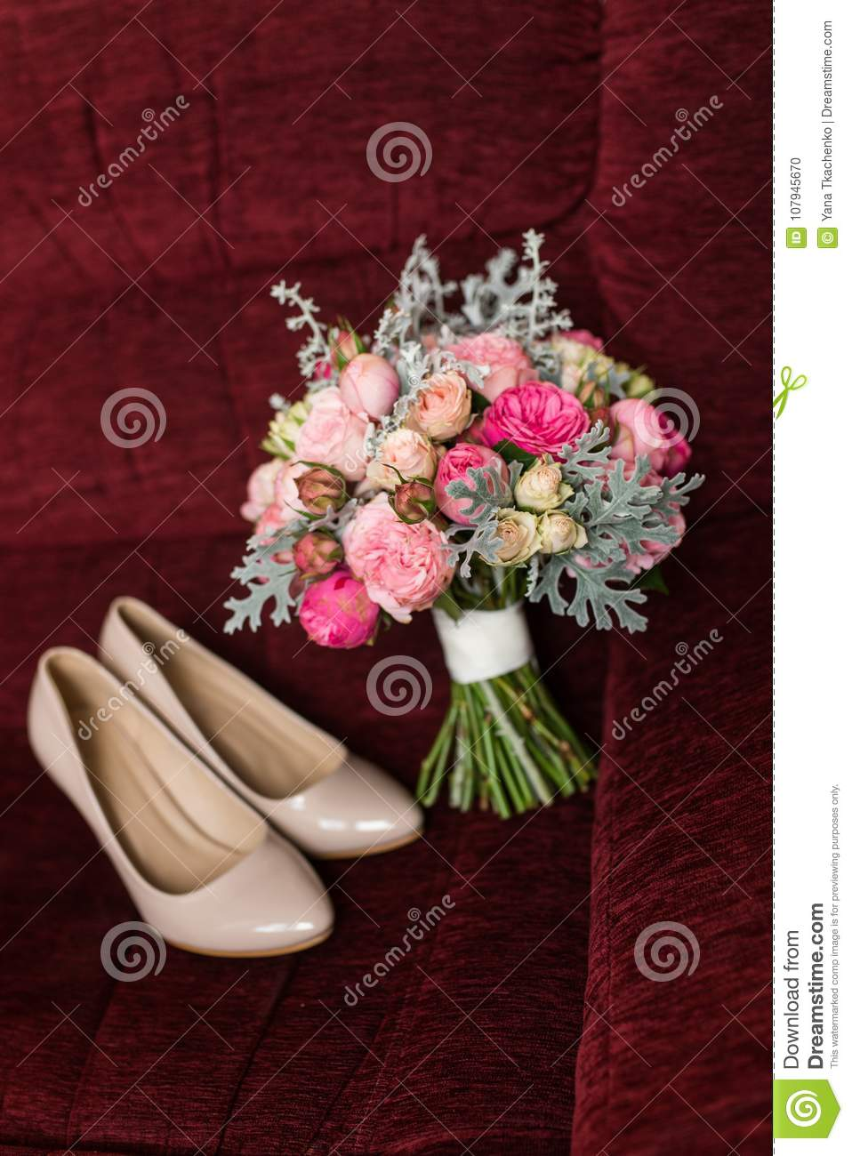 Wedding Bouquet With Purple And Pink Roses Lying On A Red Armchair