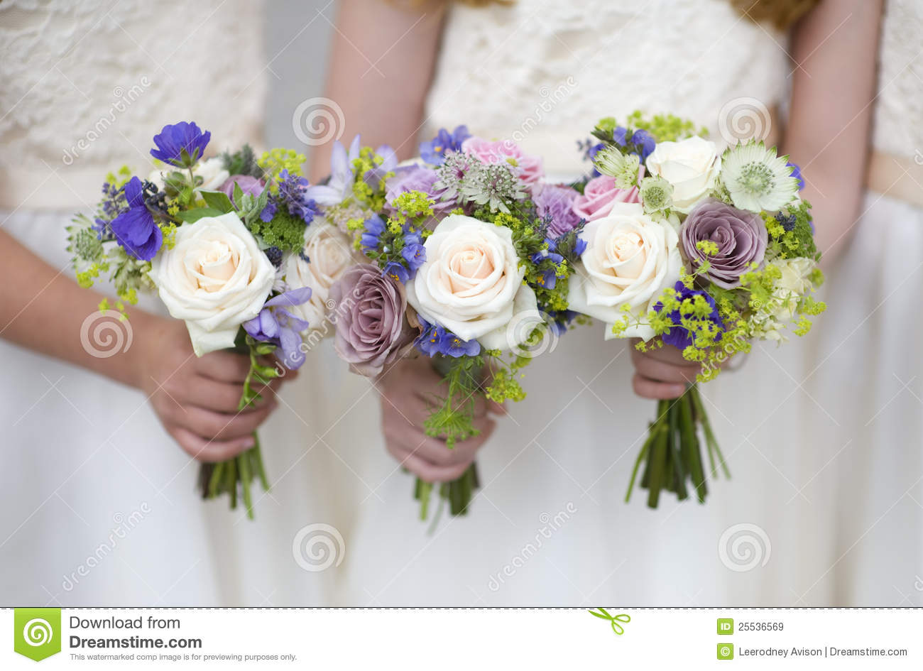 three wedding bouquets held by bridesmaids or flowergirls