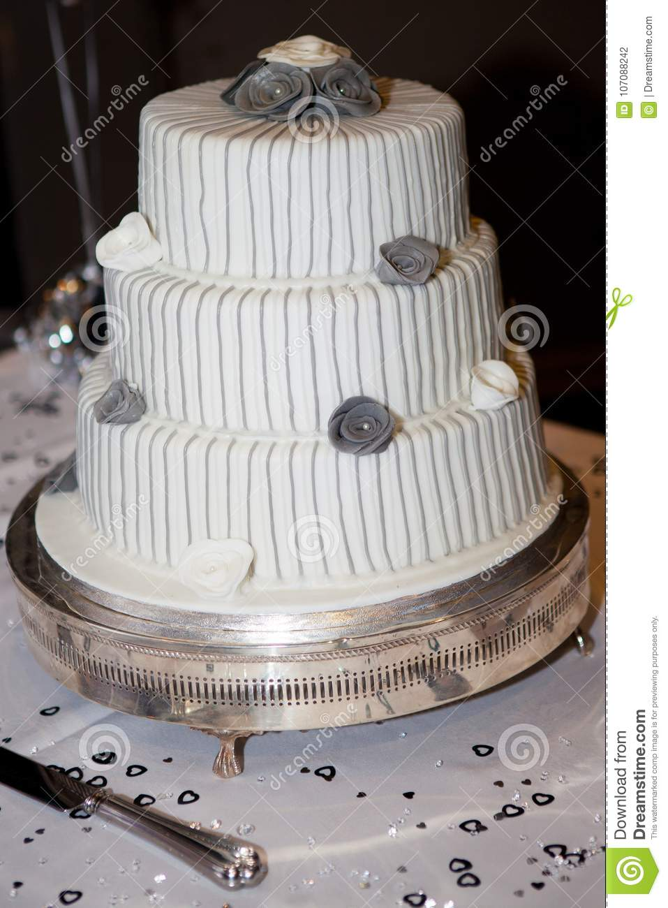 A Wedding Cake With Grey And White Flowers Decorating The Top Stock