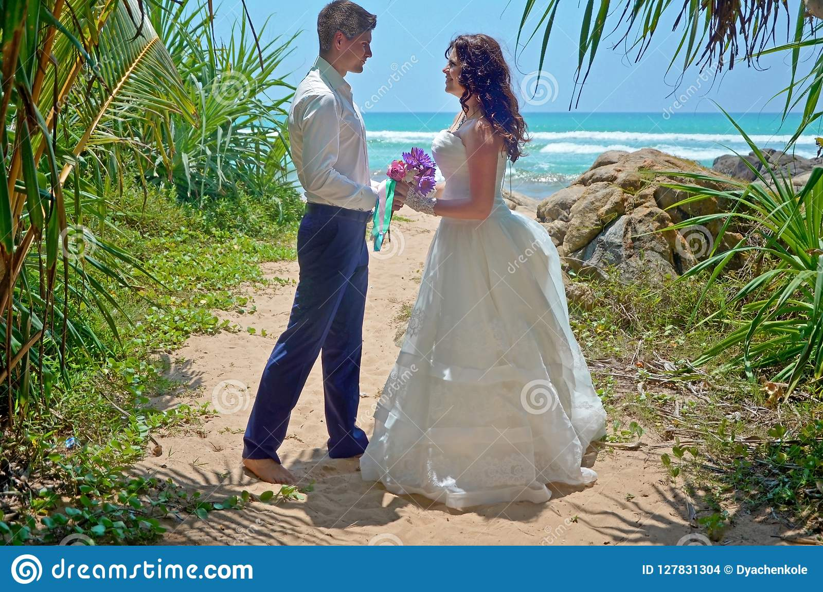 Wedding ceremony on beach in tropical palm tree, wedding and honeymoon. Beautiful bride and groom in the tropics on the island