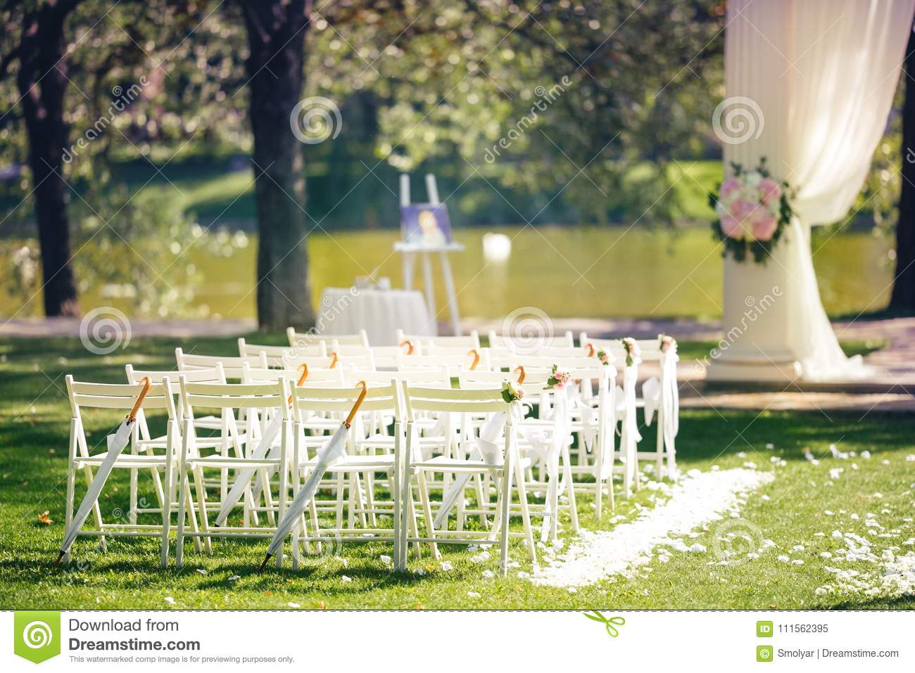 Wedding Ceremony Decoration With Chairs And Arch Near The Lake