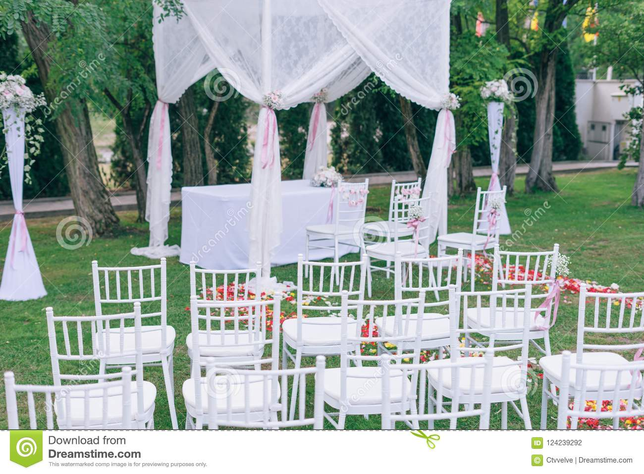 Wedding Or Ceremony Set Up In Garden, White Chairs Stock Photo