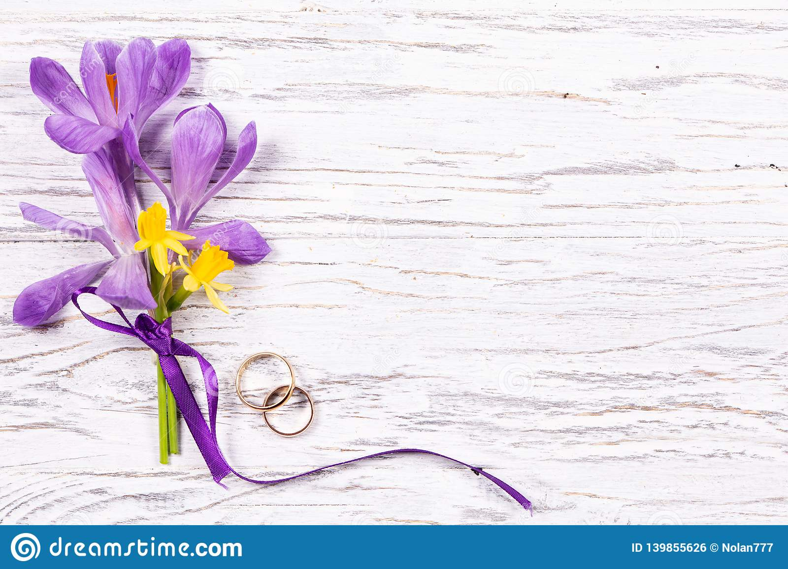 Wedding concept with spring flowers and two golden rings