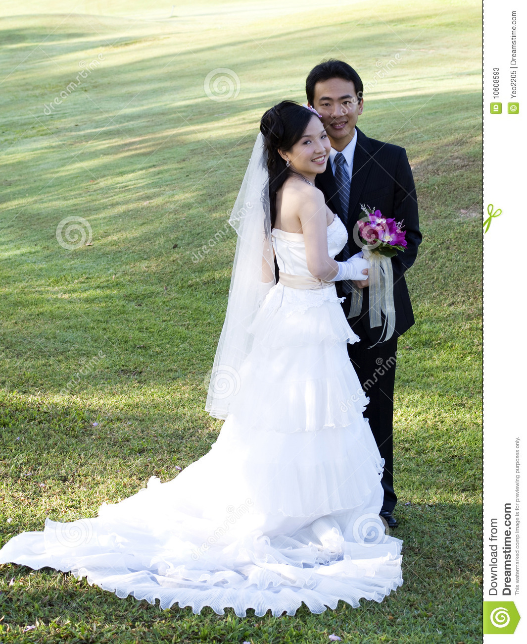 Wedding couple holding flower bouquet smiling in the golf course.