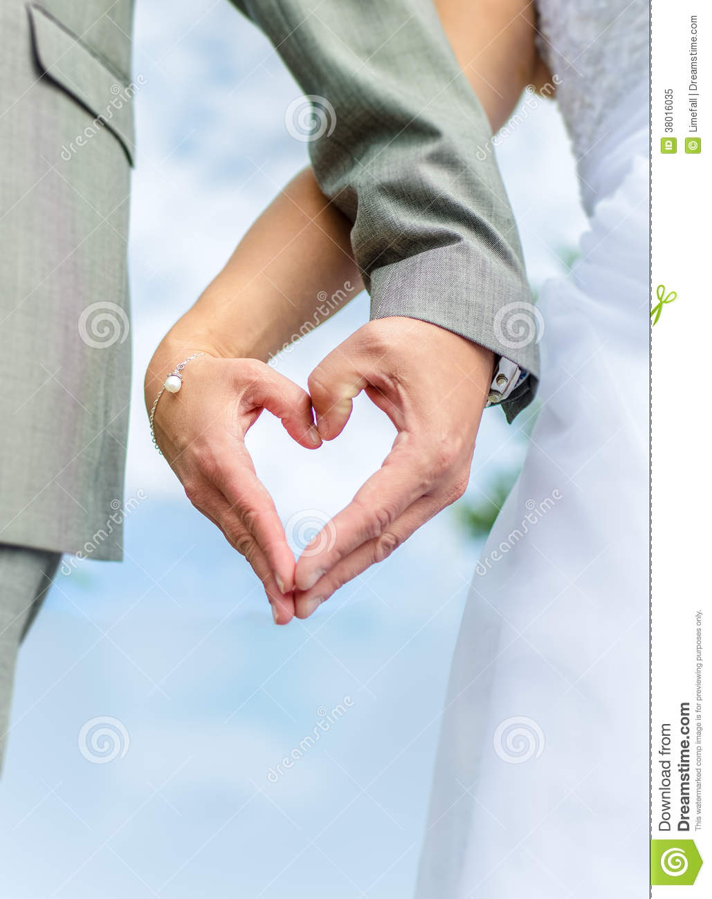 wedding couple holding theri hands in the shape of a heart.