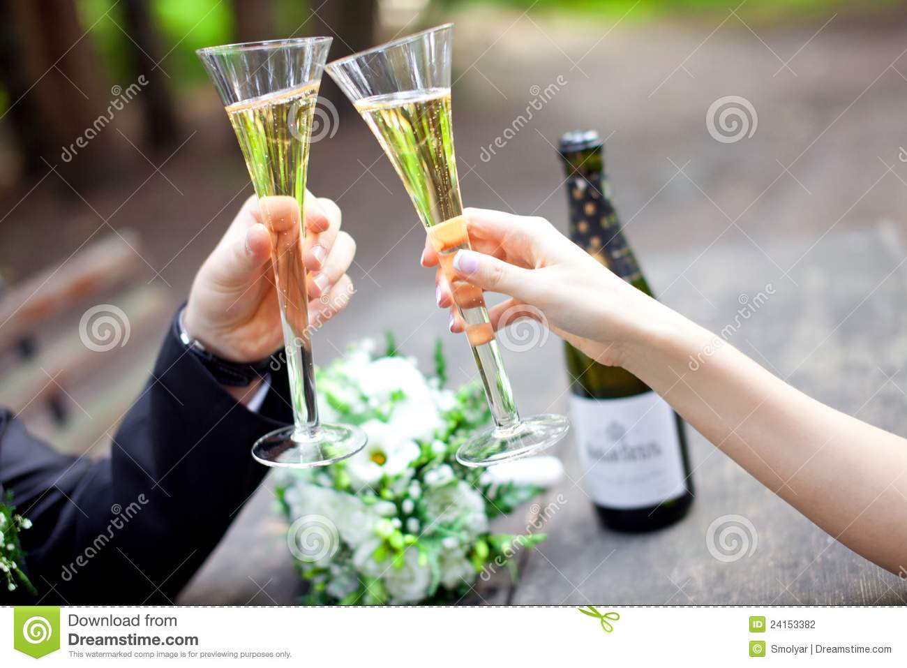 Wedding couple holding champagne glasses together