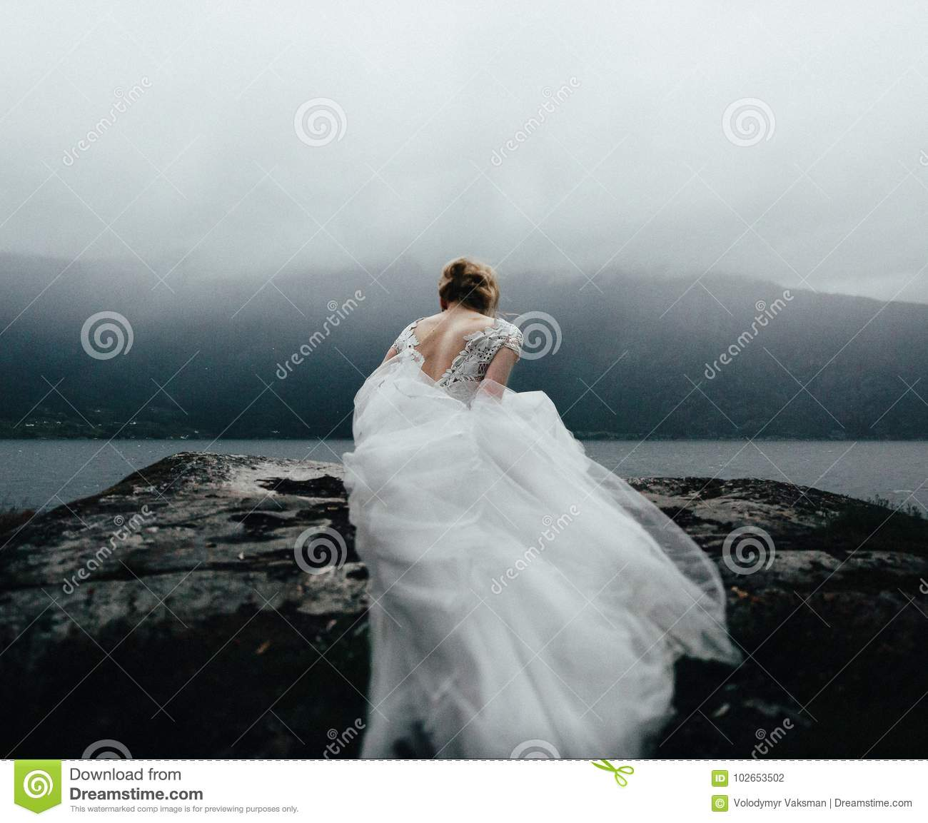 Wedding Couple Kissing And Hugging On Rocks Near Blue Sea
