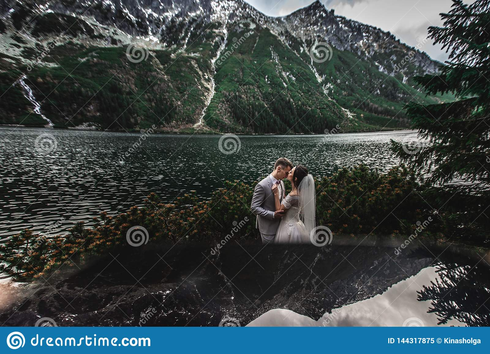 Wedding couple kissing near the lake in Tatra mountains in Poland. Morskie Oko. Beautiful summer day