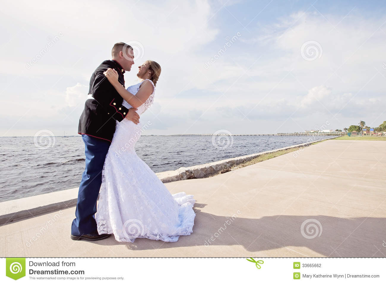 3bcb882e407847 A military groom in uniform holding his bride on a pier by the water.