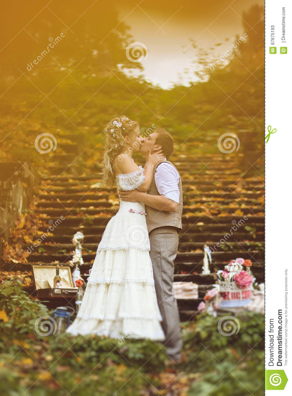 Wedding couple in a rustic style kissing near the stone steps surrounded by wedding decor at autumn forest