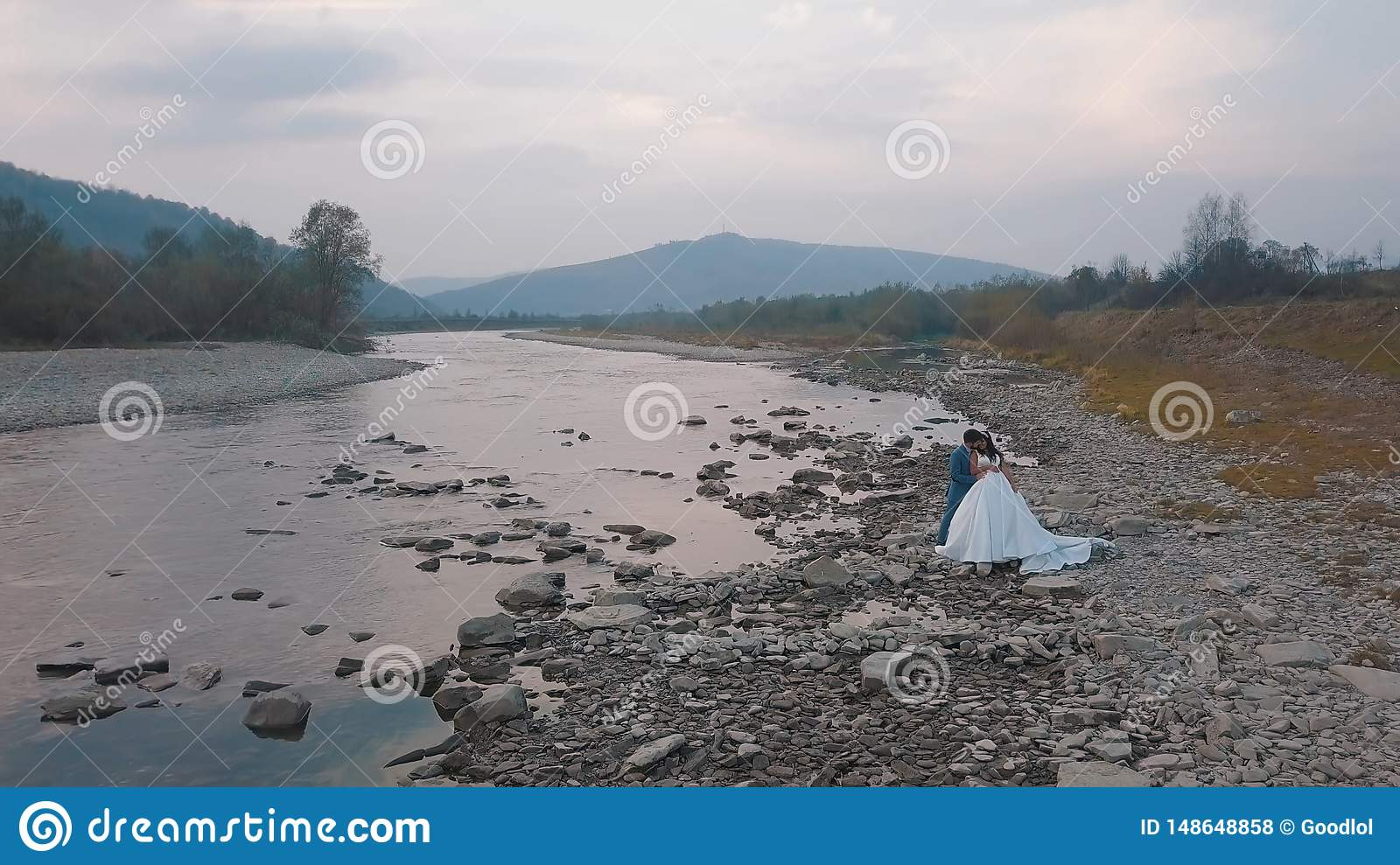 Wedding couple stand near mountain river. Groom and bride. Arial view