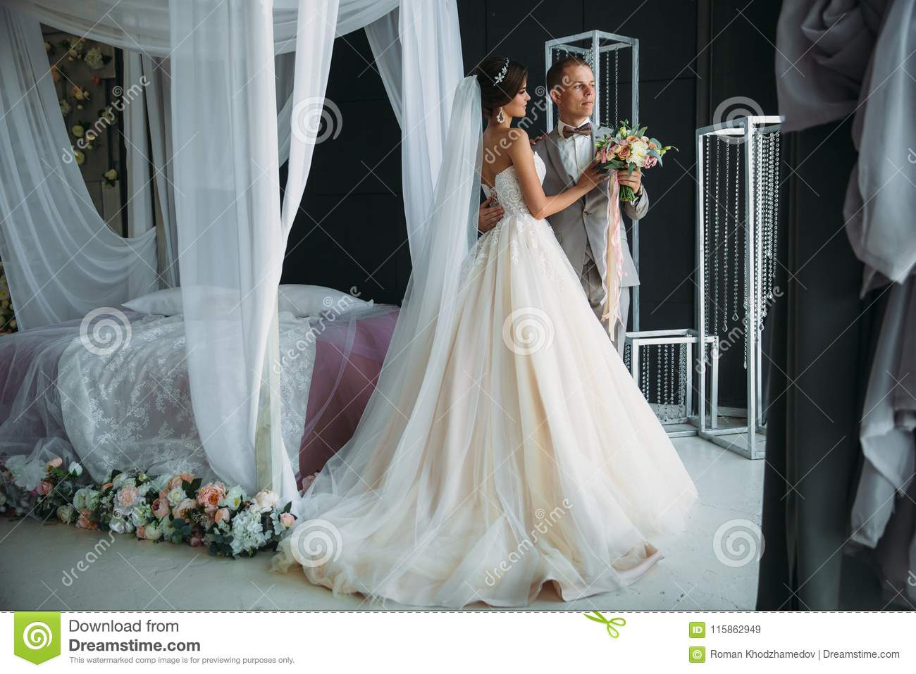 Wedding Day, Bride And Groom Hugging In Bright Studio. Men In Grey ...