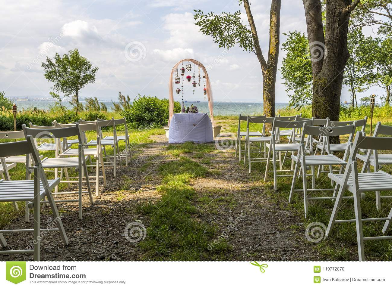 Wedding Decoration Of White Chairs, Arc Of Flowers Awaits Its