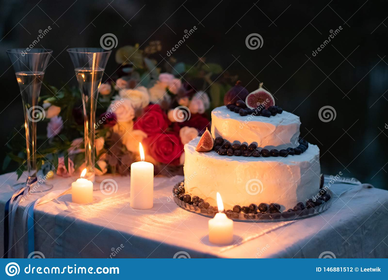 Wedding decorations. cake in white glaze with a decor of blueberries and figs on the table in the evening with glasses, lit
