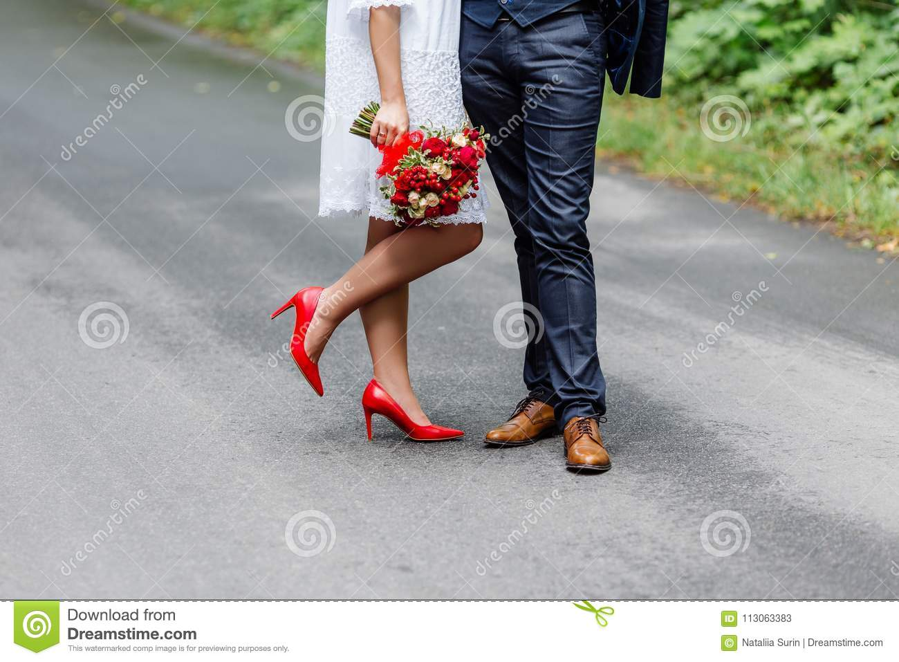 Wedding details  stylish red and brown shoes of bride and groom. Newlyweds  standing in front of each other. Bridal bouquet of roses in the hands. 13574c29f
