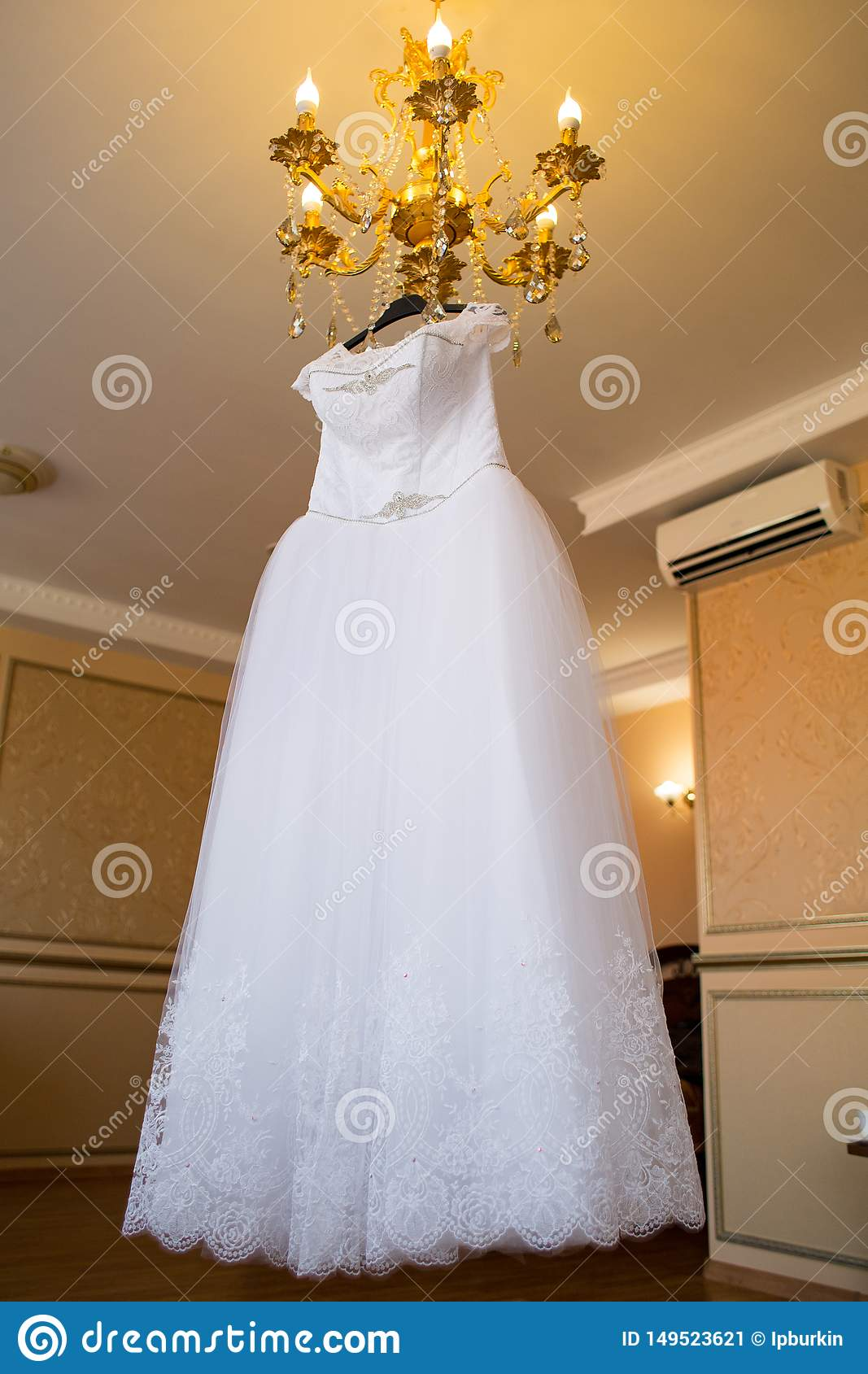 Wedding dress hanging on the chandelier. bride accessories. charges of the bride. bride`s morning