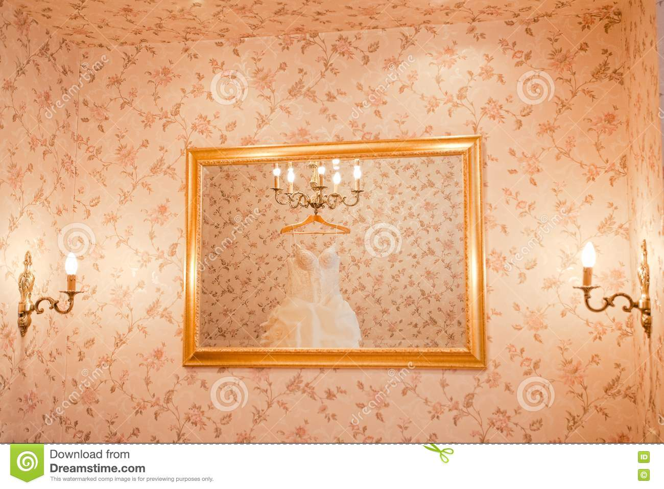 White wedding dress is reflecting in the mirror on the wall