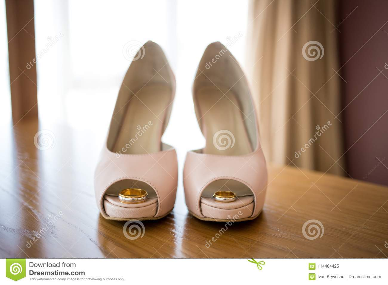 Wedding rings inside bride`s pink shoes. Ceremony