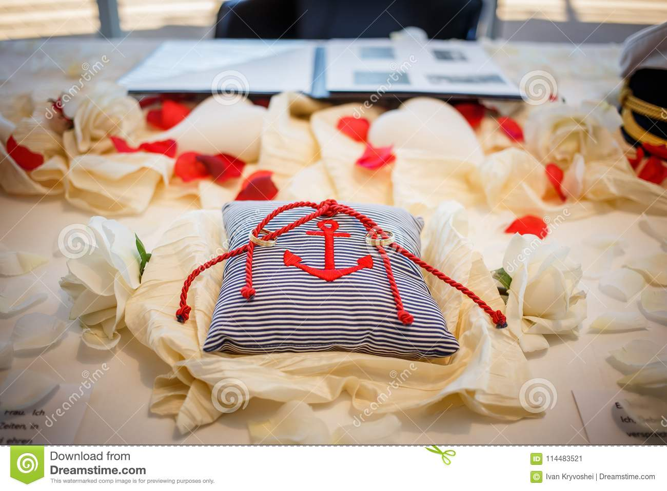 Wedding Rings Together With Red Rope On Striped Pillow With Anchor