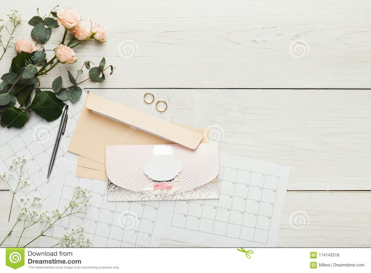 wedding invitation cards and envelopes on white wooden table to