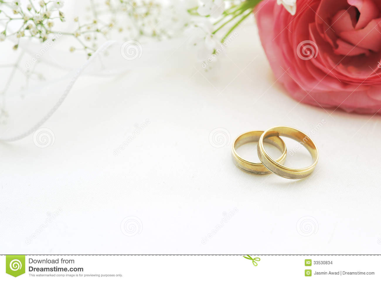 Wedding rings on silk with flowers and copy space.