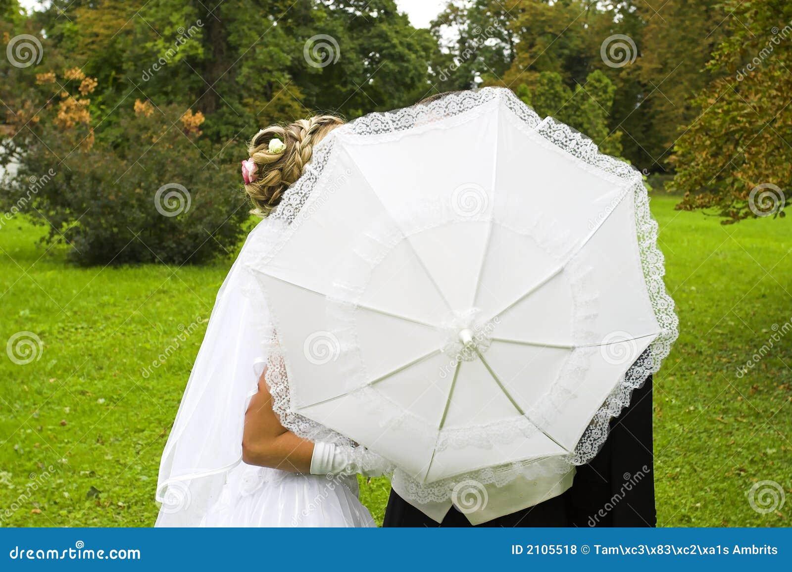 Wedding kiss behind umbrella