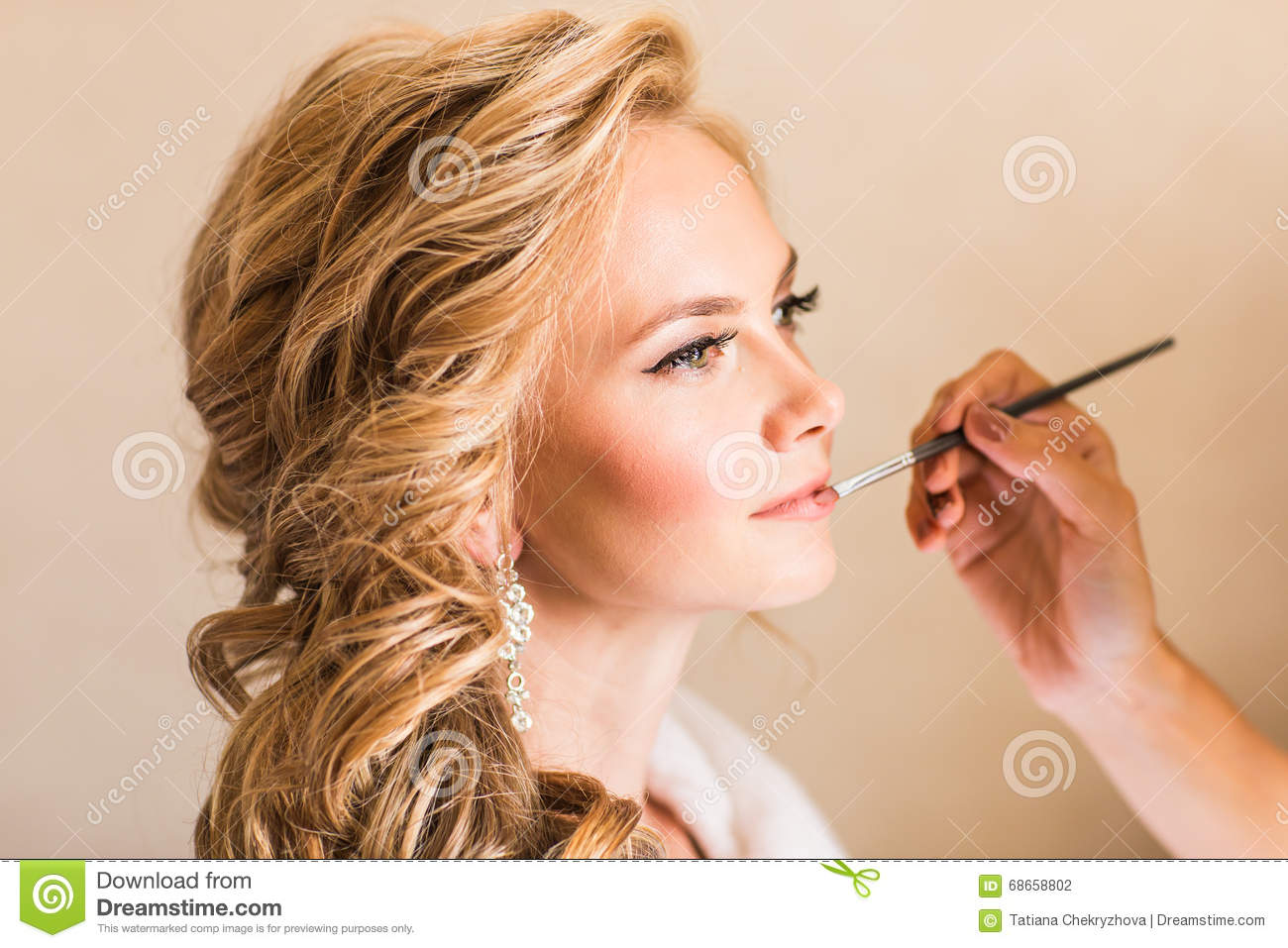 Wedding makeup artist making a make up for bride. Beautiful model girl indoors. Beauty blonde woman with curly hair