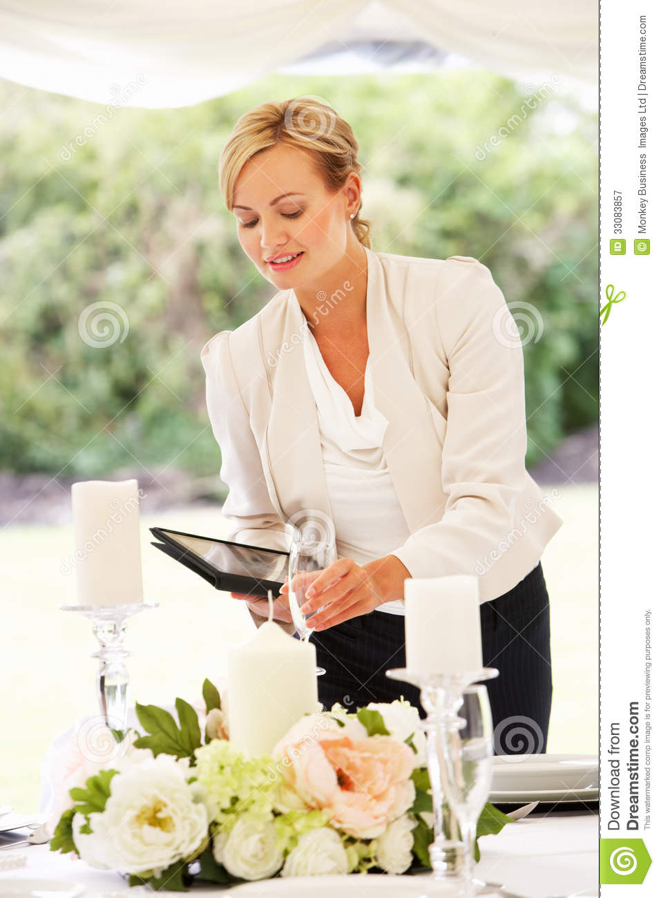 Wedding planner checking table decorations in marquee for Wedding planner decoration