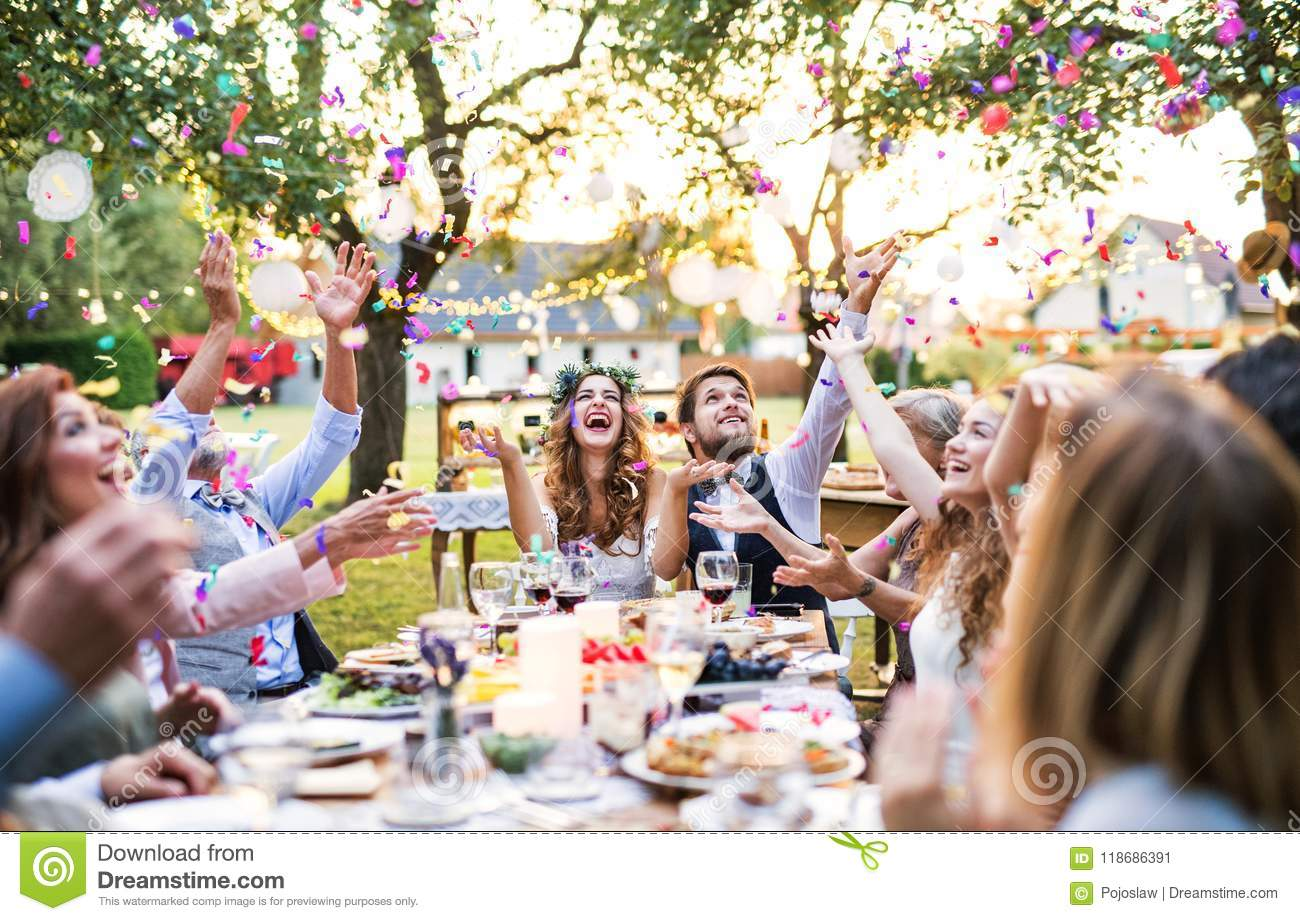 Bride And Groom With Guests At Wedding Reception Outside In The