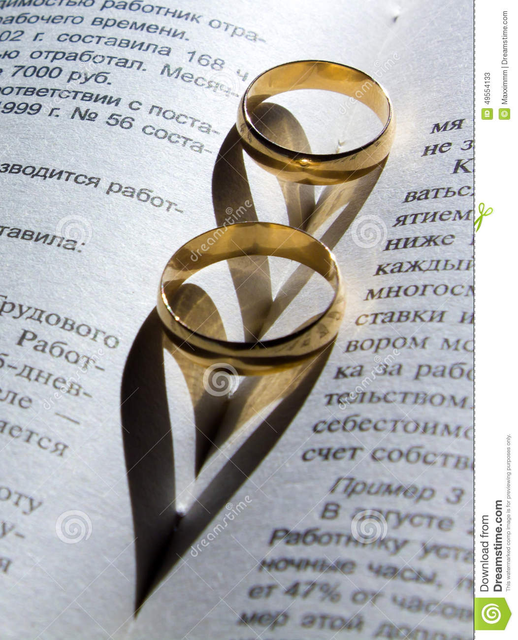 Wedding Ring On A Book With A Shadow In The Shape Stock Image