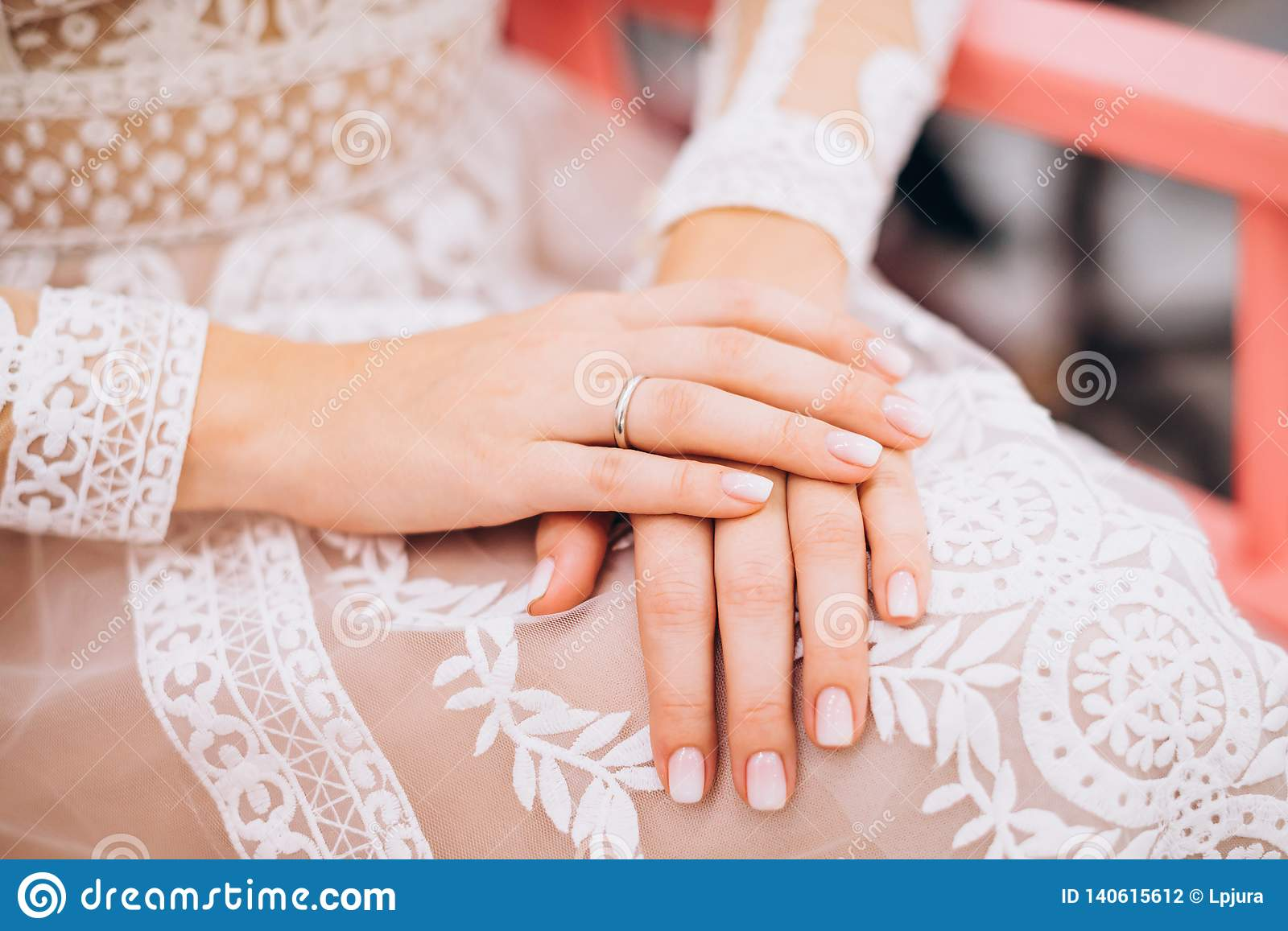Wedding Ring On The Hand Of The Bride Lying On A Wedding Dress