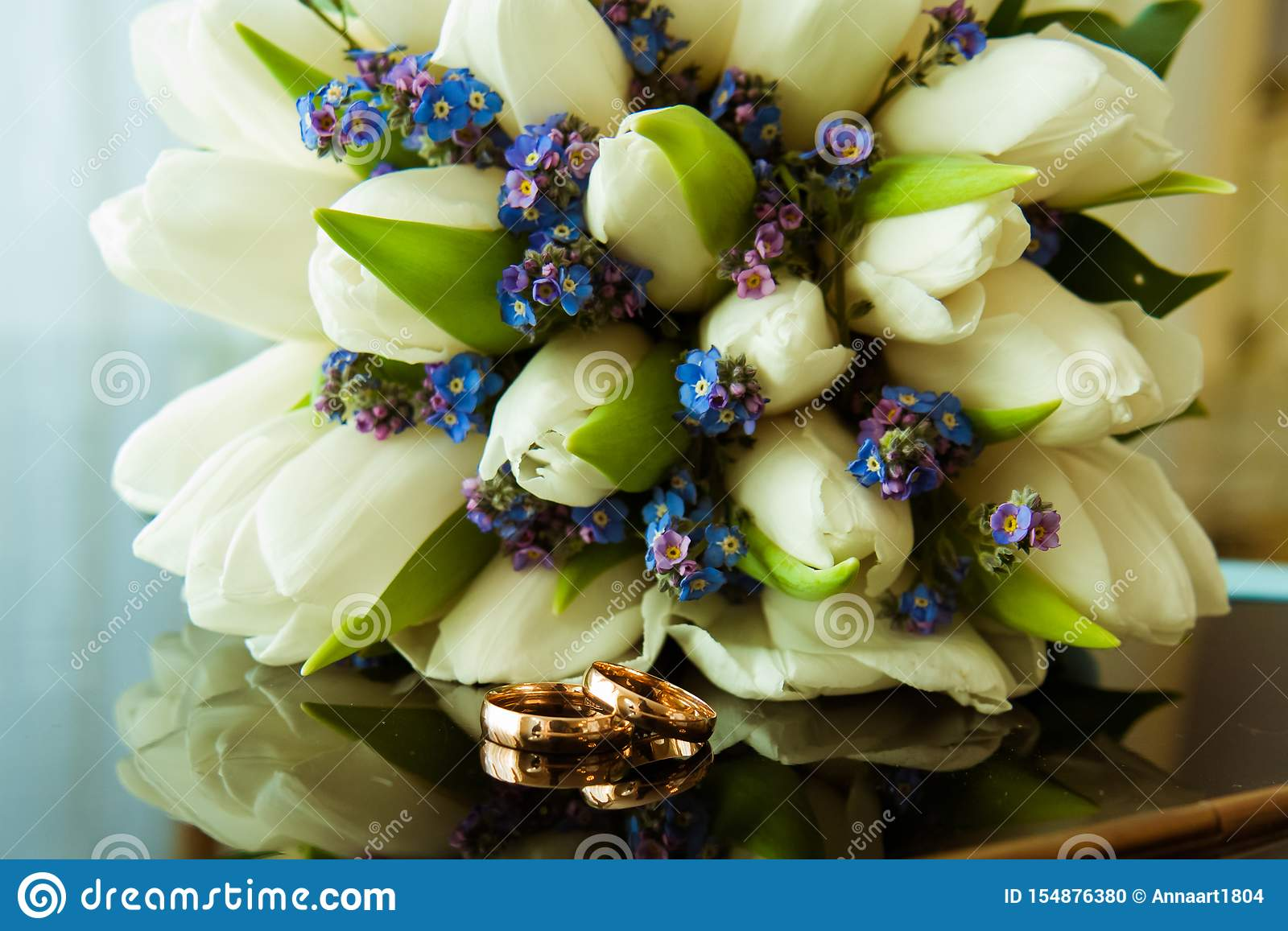 Wedding rings of the bride and groom on a Beautiful wedding bouquet of white tulips