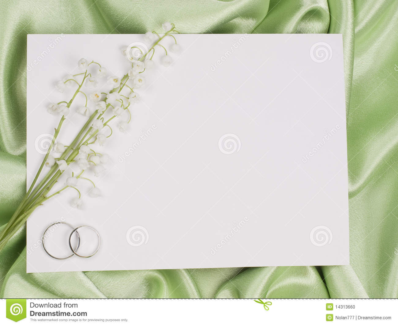 Wedding rings, card and lily of the valley